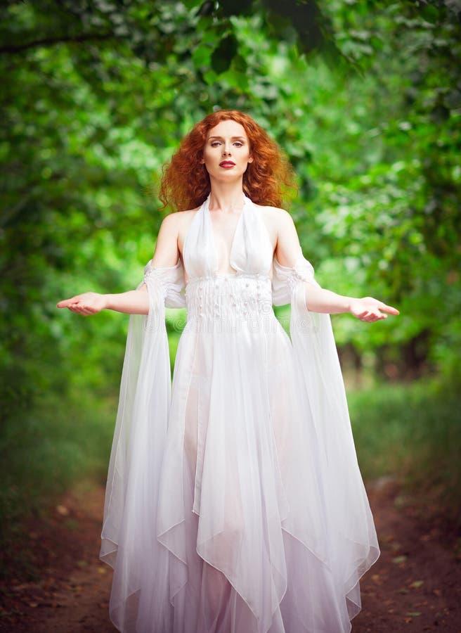 Vestito bianco d'uso dalla bella donna della testarossa in una foresta immagini stock