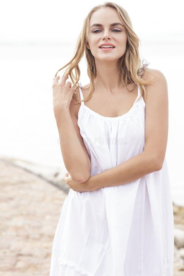 Vestito bianco d'uso dalla bella giovane donna fotografie stock libere da diritti