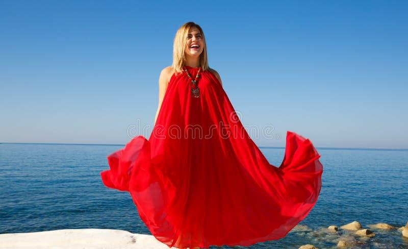 Vestito biondo dalla donna in rosso fotografia stock