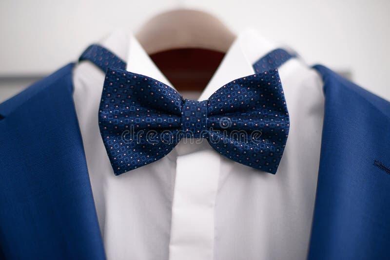 Vestito blu elegante del primo piano con la camicia bianca ed il farfallino blu, in preparazione di un evento convenzionale fotografia stock
