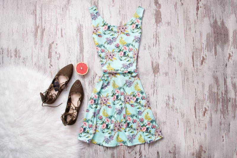 Vestito blu in fiori e scarpe marroni Fondo di legno, concetto alla moda fotografie stock