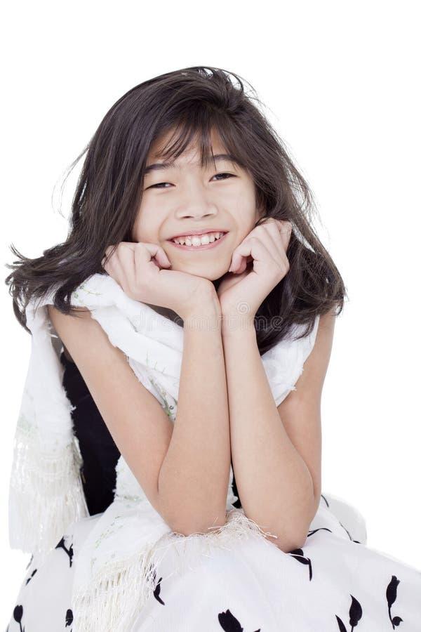 Vestito convenzionale, seduta e sorridere dalla ragazza in bianco e nero fotografia stock libera da diritti