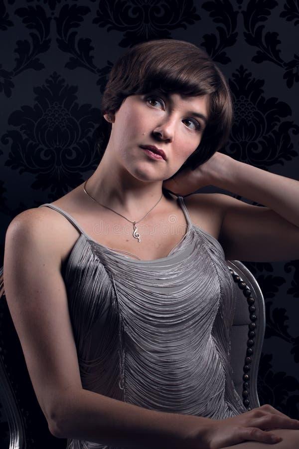 Vestito d'annata d'argento d'uso seduto bella giovane donna fotografie stock libere da diritti