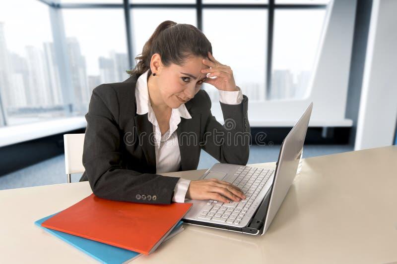 Vestito d'uso dalla donna di affari che lavora al computer portatile alla stanza moderna dell'ufficio fotografia stock libera da diritti