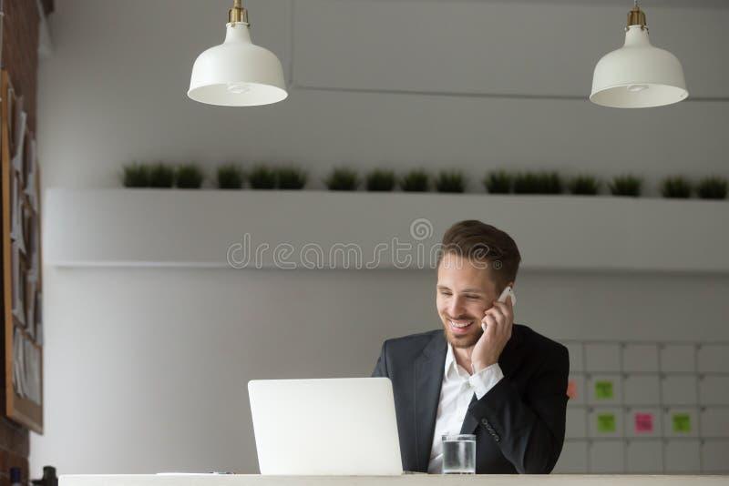 Vestito d'uso sorridente dell'uomo d'affari che parla sul telefono facendo uso del lapt immagine stock libera da diritti