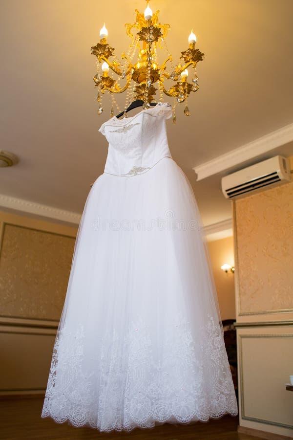 Vestito da cerimonia nuziale che appende sul lampadario a bracci Accessori della sposa spese della sposa Mattina del ` s della sp immagine stock
