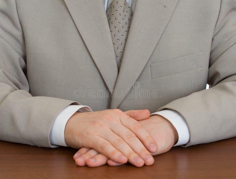 Vestito da portare dell'uomo d'affari con le mani clasped immagine stock libera da diritti