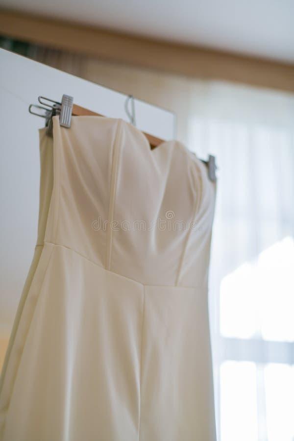 Vestito da sposa che appende sul gancio sulla porta del Governo Vertica immagini stock libere da diritti