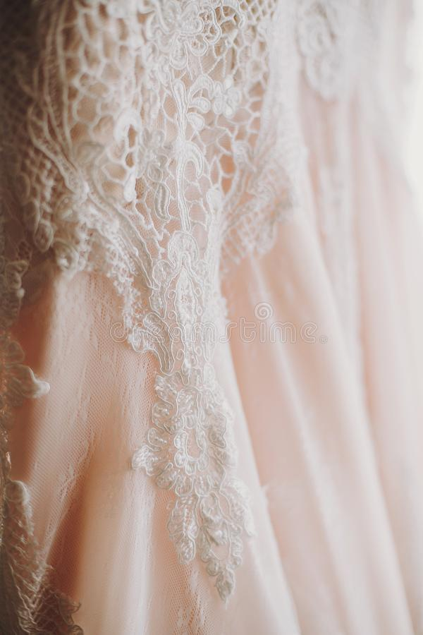 Vestito da sposa moderno di lusso che appende alla finestra Abito di nozze alla moda di stupore con i dettagli floreali del pizzo fotografie stock libere da diritti