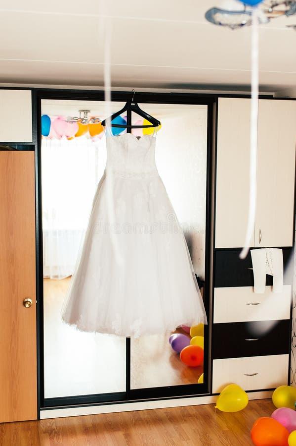 Vestito da sposa su un gancio sui precedenti dello specchio fotografie stock libere da diritti