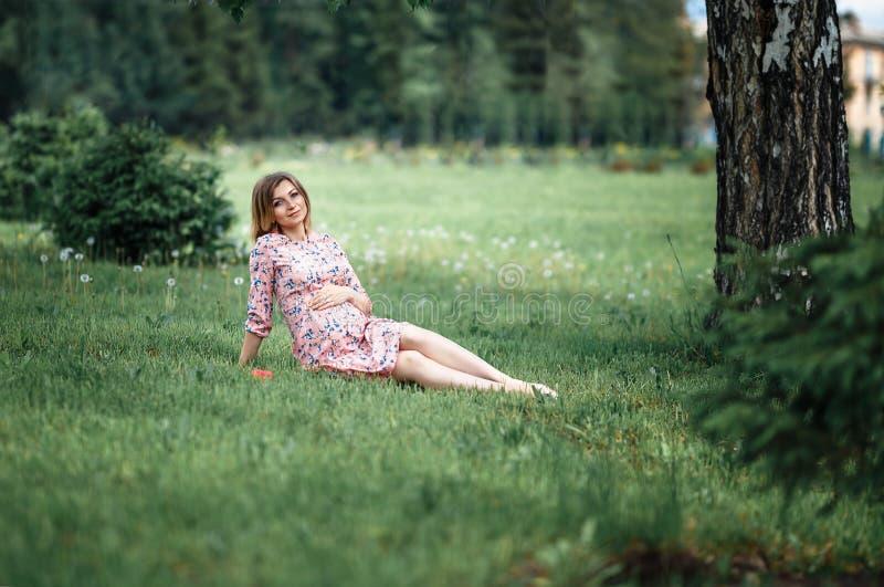 Vestito dal inpink della donna incinta che si siede sull'erba e che tocca urto mentre tenendo attesa rosa rosa della ragazza fotografia stock