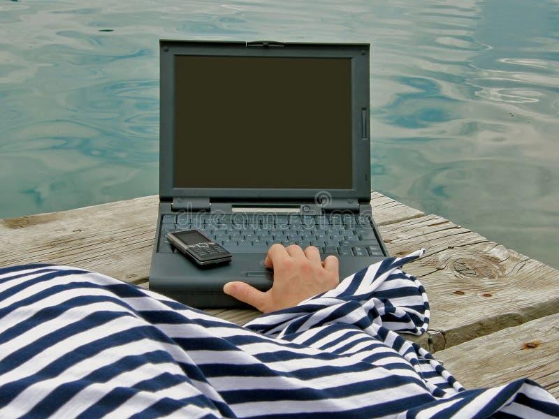 Vestito dal marinaio con cellulare ed il computer portatile fotografia stock