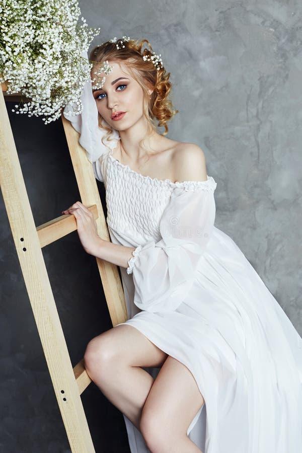 Vestito dalla luce bianca della ragazza e capelli ricci, ritratto della donna con i fiori a casa vicino alla finestra, purezza ed immagine stock