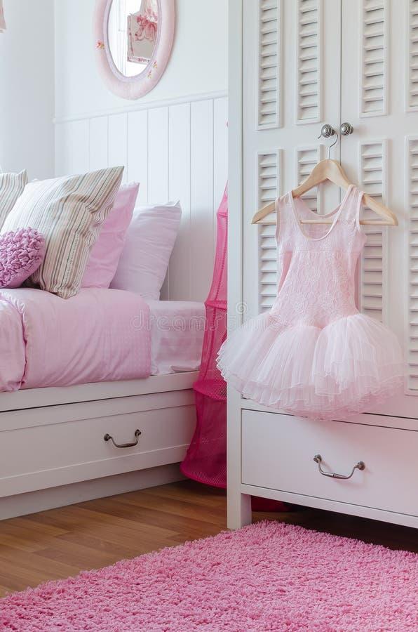 Vestito dalla ragazza che appende sul guardaroba in camera da letto fotografia stock libera da diritti