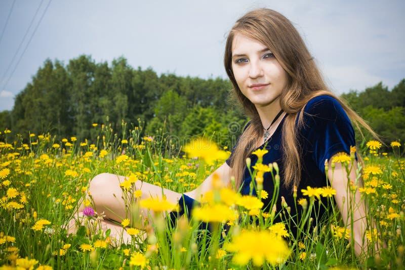 Vestito dalla ragazza nell'erba con i denti di leone immagini stock libere da diritti