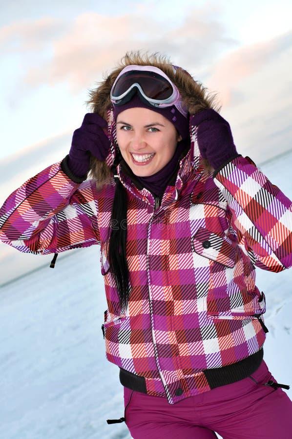 Vestito di corsa con gli sci da portare sorridente della giovane donna fotografia stock libera da diritti