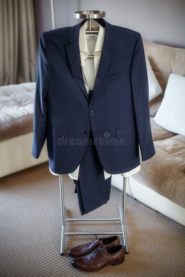Vestito di nozze, camicia, pantaloni, scarpe dello sposo che appendono sul gancio fotografia stock