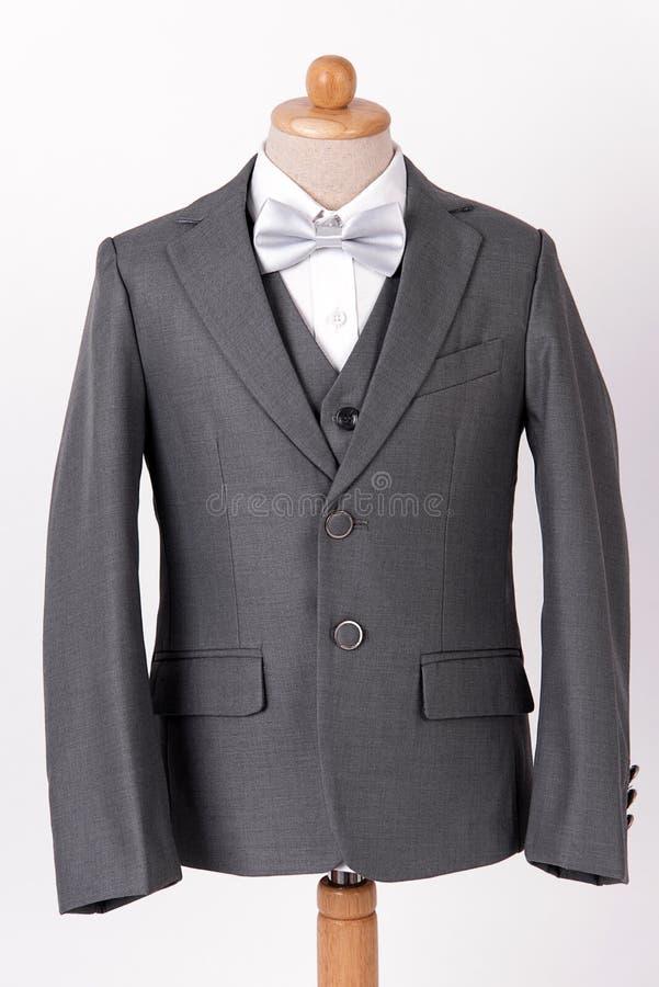 Vestito grigio del rivestimento dei bei uomini con la camicia e la cravatta a farfalla su fondo bianco immagine stock