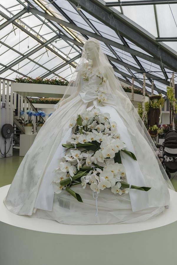 Vestito magnifico bianco della sposa con i gigli in tensione bianchi su un manichino Festa dei colori stupefacenti e dei sapori d fotografia stock
