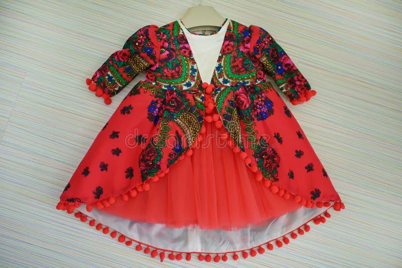 Vestito per le neonate fatte del cotone rosso della batista o della batista, con la stampa variopinta di Paisley nello stile degl fotografia stock