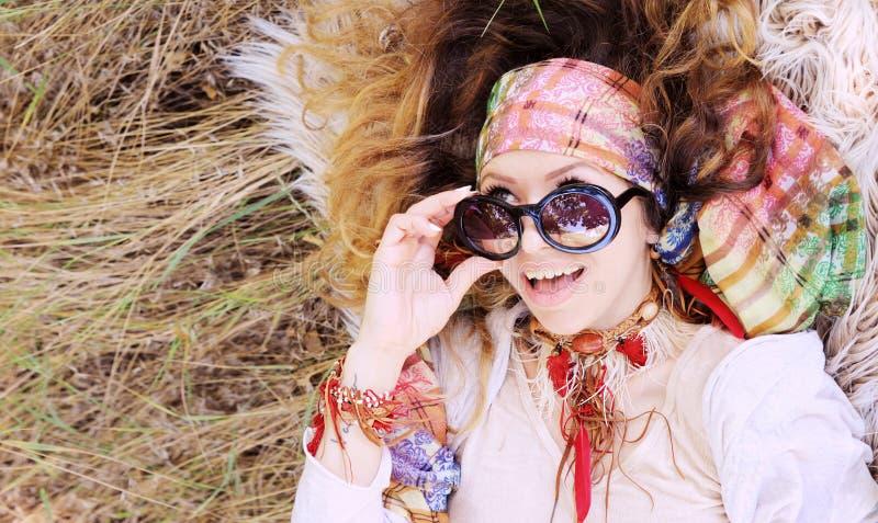 Vestito in ritratto elegante della donna di stile di boho che si trova su un fieno e su una pelliccia, sano e felice fotografia stock