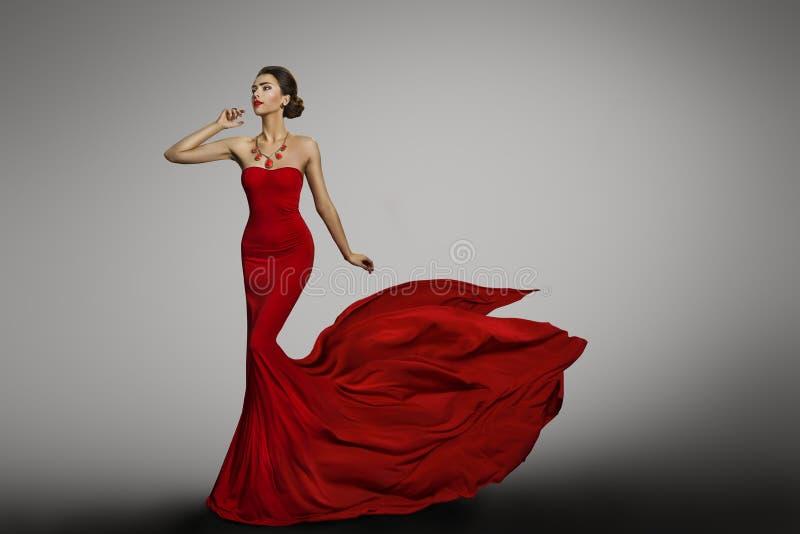Vestito rosso dalla donna, modello di moda in abito sexy di seta d'ondeggiamento lungo immagine stock libera da diritti