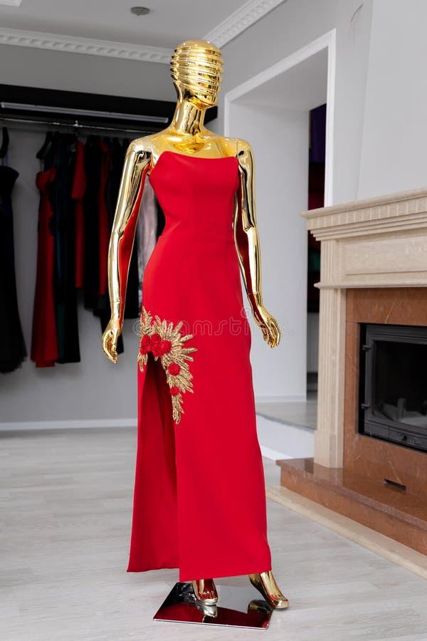 Vestito rosso femminile e lungo con l'ornamento dalle perle dorate su un manichino dorato immagine stock