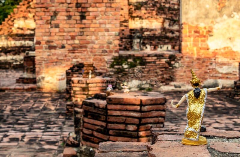 Vestito tailandese dalle bambole sui mattoni del pavimento in un tempio abbandonato fotografie stock