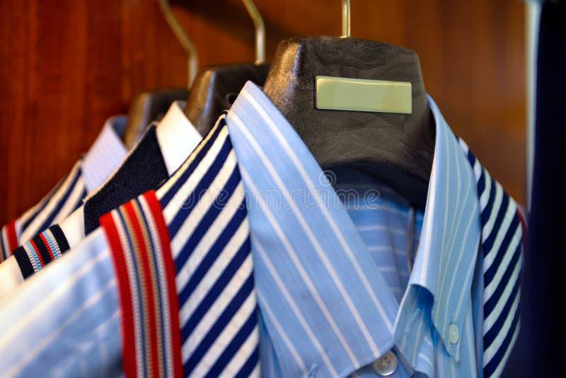 Vestuário com texturas listradas e lisas clássicas das camisas, o armário armazenado, negócio da roupa da roupa fotografia de stock