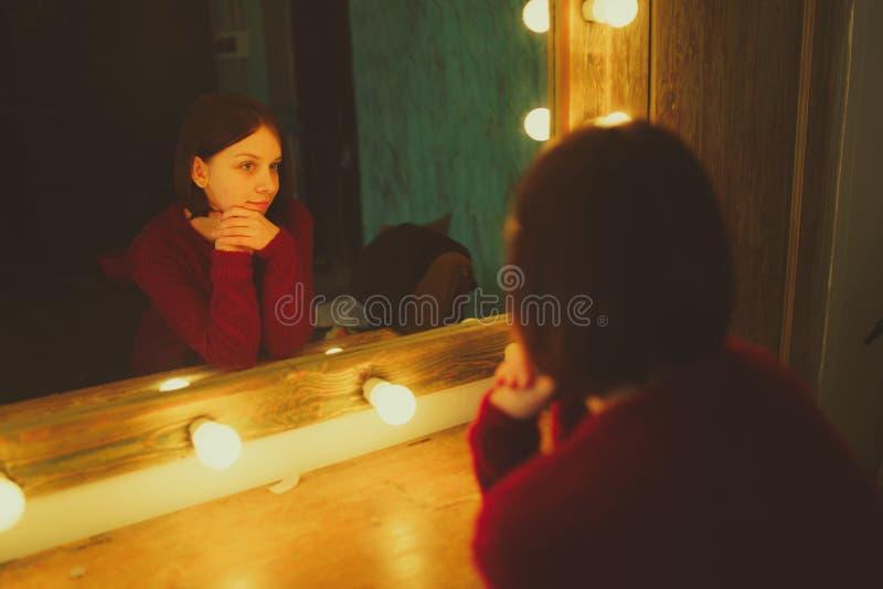 Vestuário, forma, estilo e conceito dos povos - mulher feliz que olha a reflexão de espelho imagens de stock