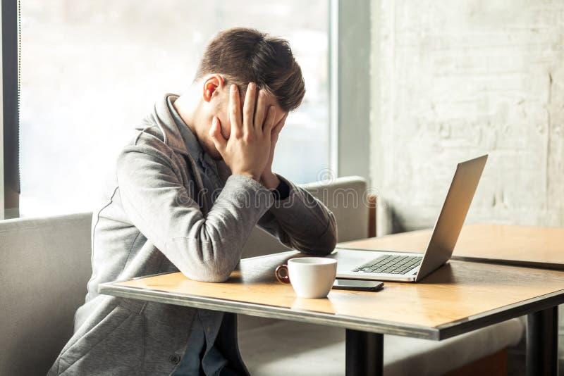 Vet inte! Ståenden av den ledsna trötta bara deprimerade trötta skäggiga unga freelanceren i grå blazer sitter bara i kafé och royaltyfri foto