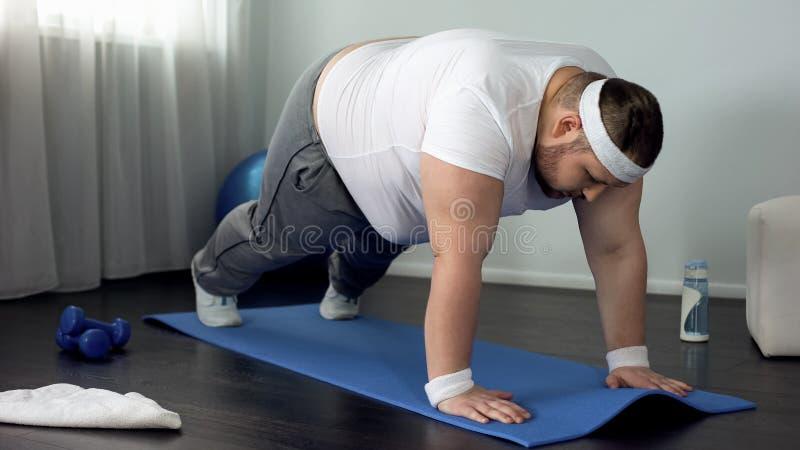 Vet mannetje die duw op oefening proberen te doen thuis, zwakke spieren, gebrek aan motivatie stock afbeeldingen