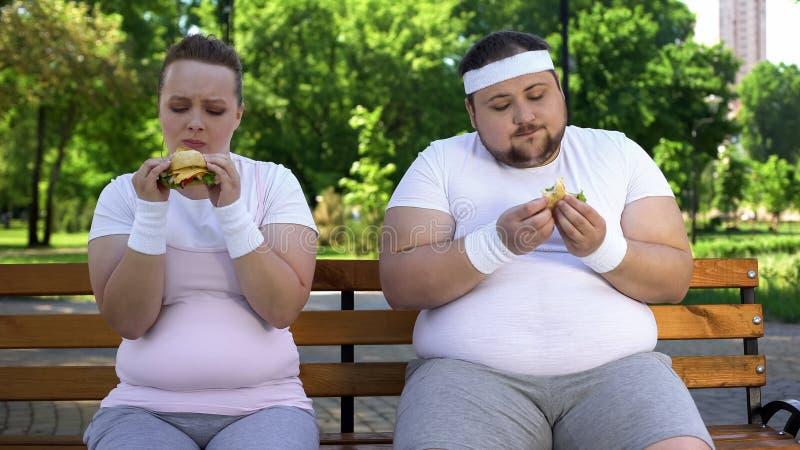 Vet paar die burgers eten, die schuldig voor het tegenhouden van dieet, snel gewijd voedsel voelen royalty-vrije stock foto's