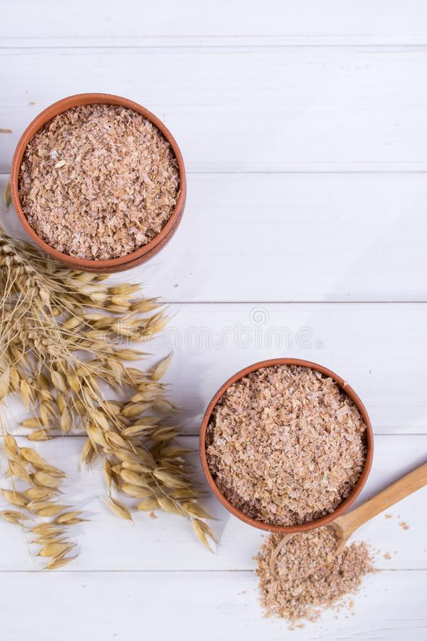 Vete-, havrekli i lerabunke och öron av vete och havren Diet-tillägg som förbättrar matsmältning arkivfoton