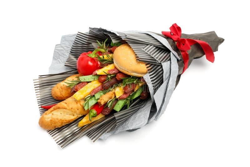 Vetebröd, sesambullen, ost av olika variationer, korvar och peppar slås in i grått papper som en gåvabukett på ett vitt royaltyfria foton