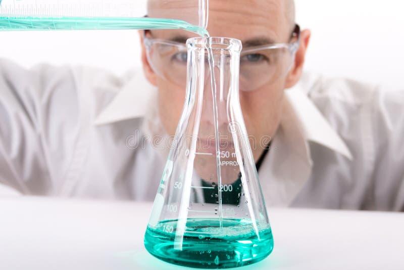 Vetenskap Guy Filling Erlenmeyer Flask With Teal Liquid royaltyfri bild