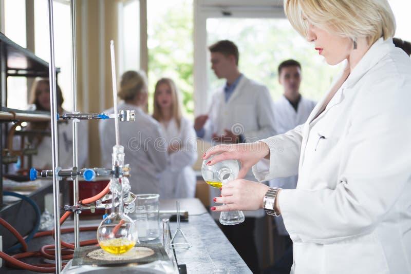 Vetenskaplig forskare som gör en kemisk experimentforskning Vetenskapsstudenter som arbetar med kemikalieer Kemist som gör forskn arkivfoto