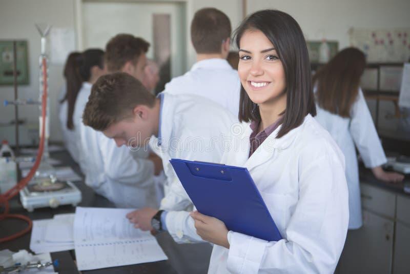Vetenskaplig forskare som rymmer en mapp av kemisk experimentforskning Vetenskapsstudenter som arbetar med kemikalieer i labbet p arkivfoto