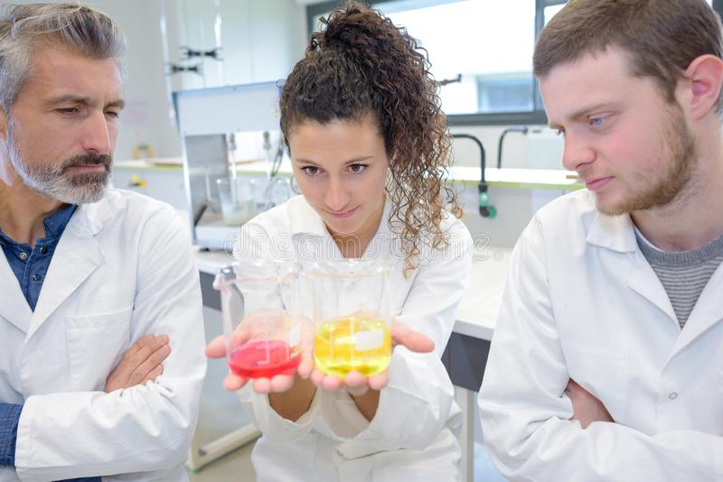 Vetenskapligt forskareinnehav på vätskelösningen i labb arkivbild