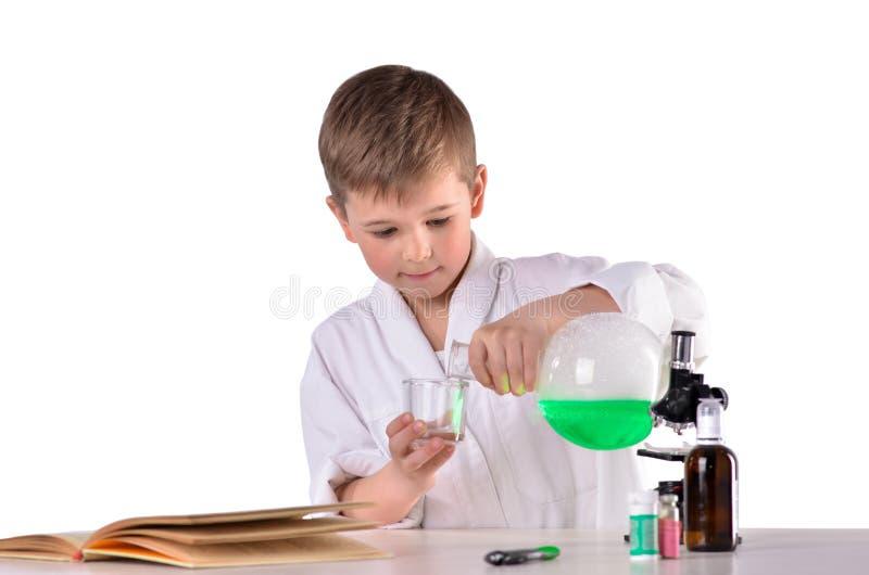 Vetenskapspojken häller flytande från flaskan in i exponeringsglas royaltyfria foton