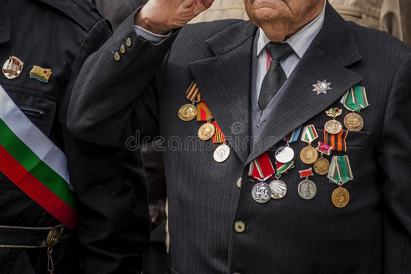A veteran decorated with medals and orders on the costume gives honor during a parade. Veteran of the war with numerous medals on the chest royalty free stock photos