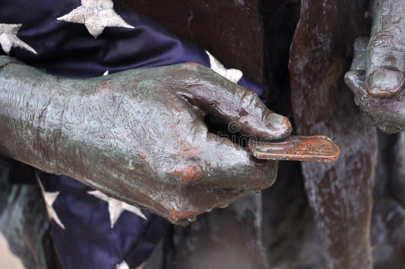 Veteran, der dogtag und Flagge am Vietnamkriegdenkmal hält stockbild