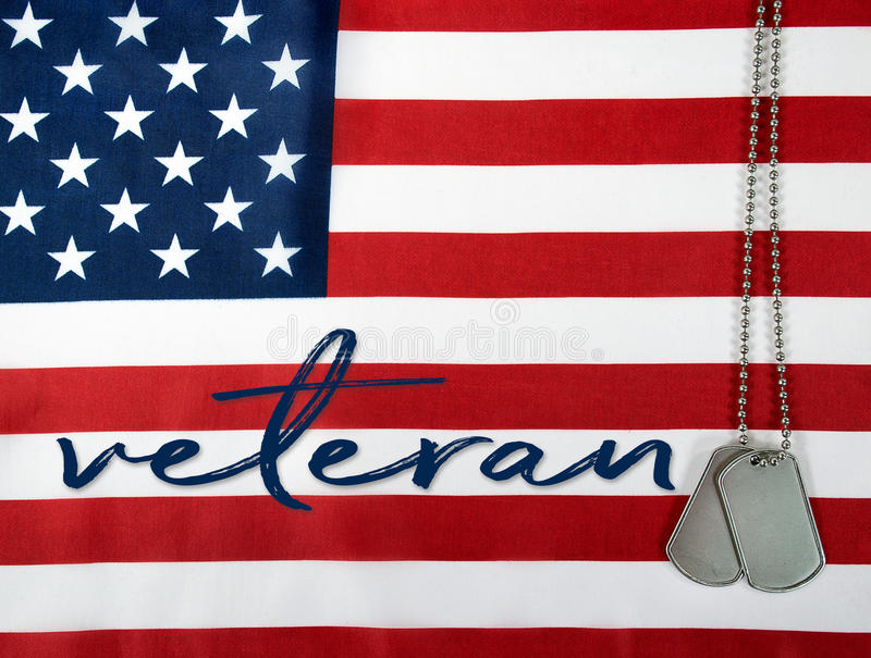 Veteran dog tags on American flag. Word veteran and military dog tags on American flag background royalty free stock images