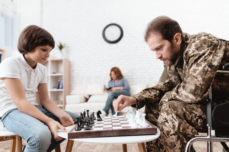 Veteran i militär likformig i en rullstol En handikappade personerman spelar med hans son i schack royaltyfria foton