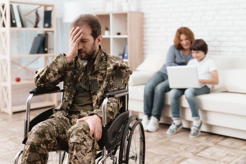 Veteran i rullstolen som gås tillbaka från armén Mannen i en rullstol är smärtar in Honom ` s i militär likformig royaltyfri fotografi