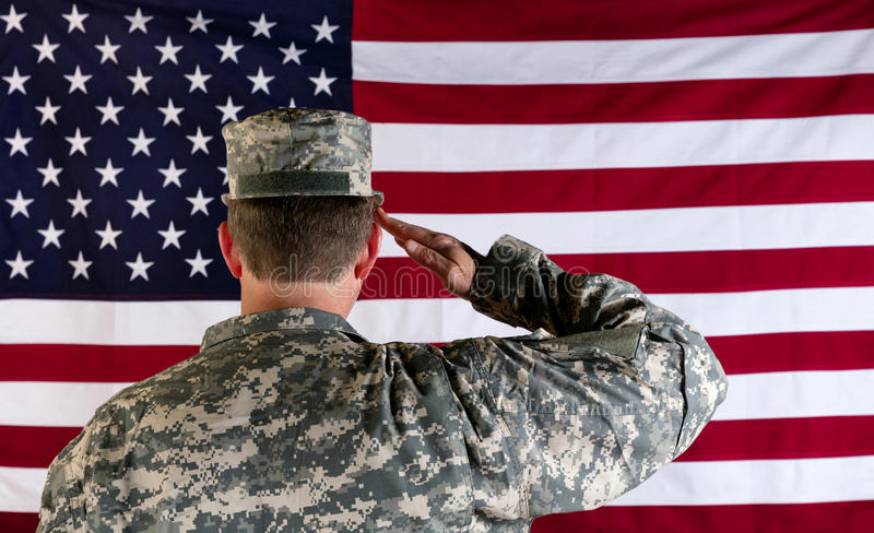 Veteran male solider saluting the flag of USA royalty free stock photos