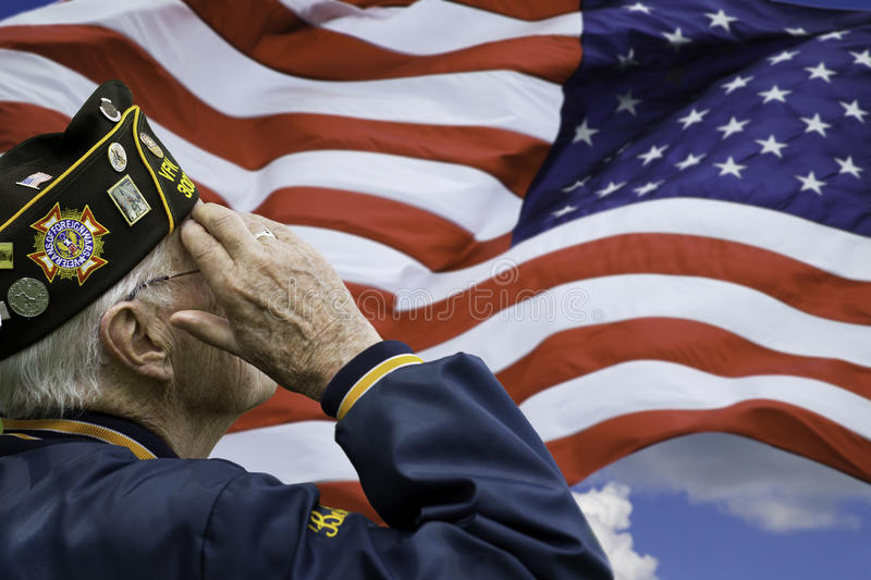 Veteran's Saluting. A veteran is saluting in front of US flag royalty free stock photo