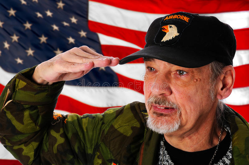 Veteran Salutes. Vietnam veteran standing in front of United States flag saluting royalty free stock photo