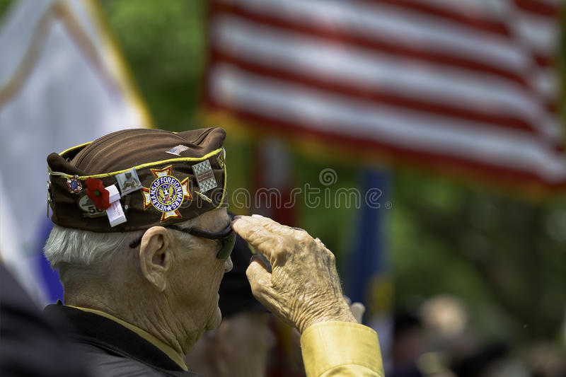 Veteran Saluting. Veteran Salutes the US Flag royalty free stock image