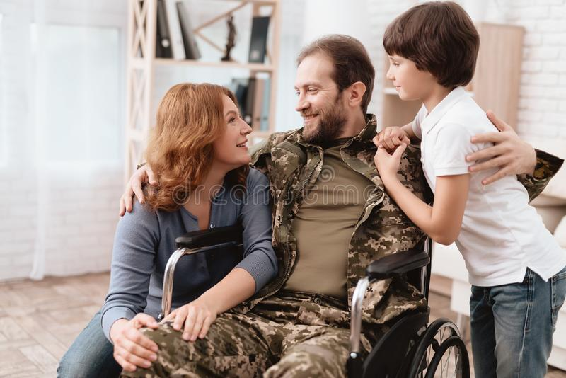 The veteran in a wheelchair came back from the army. A man in uniform in a wheelchair with his family. stock image